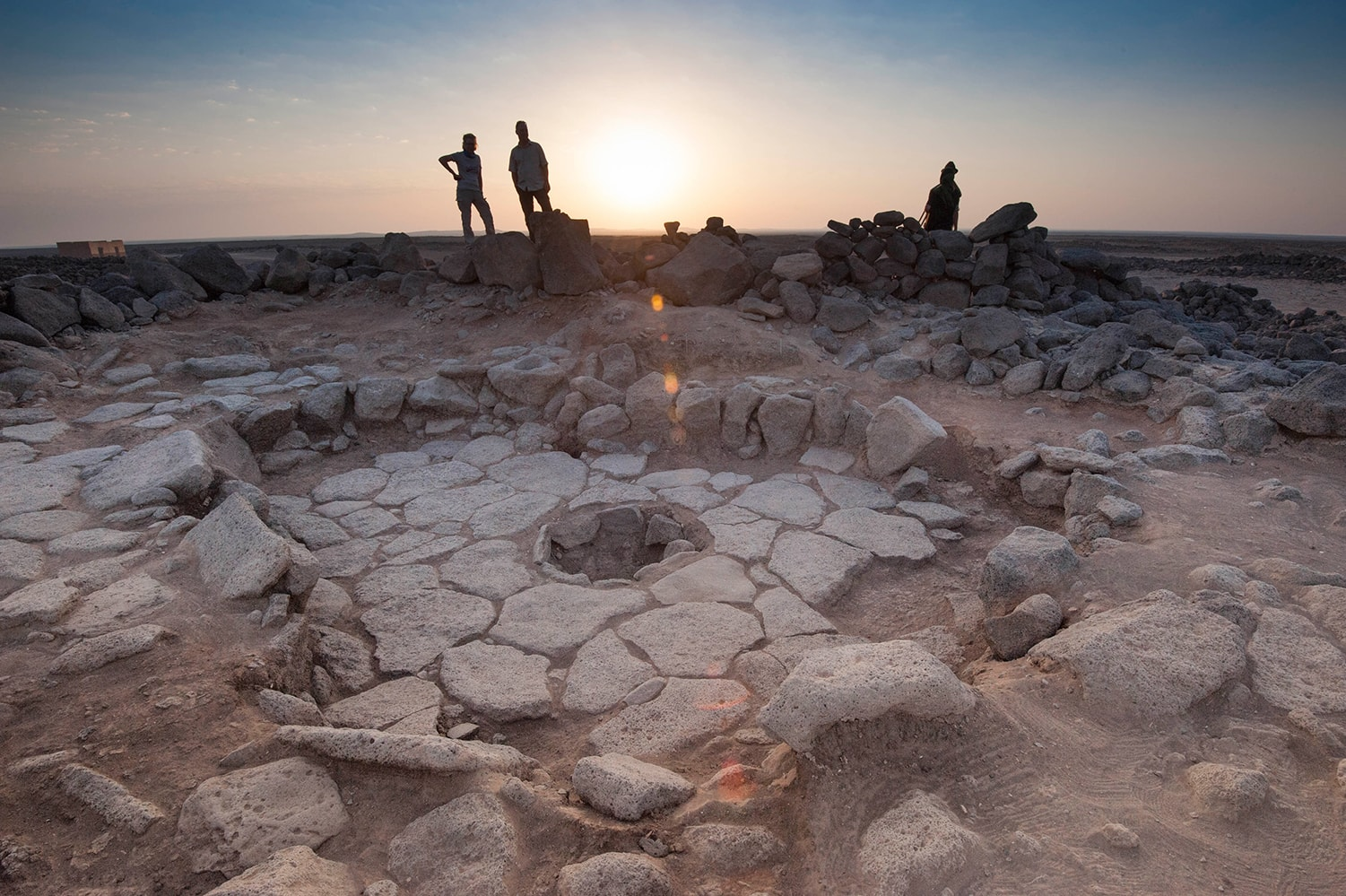 Researchers standing around stone oven structure