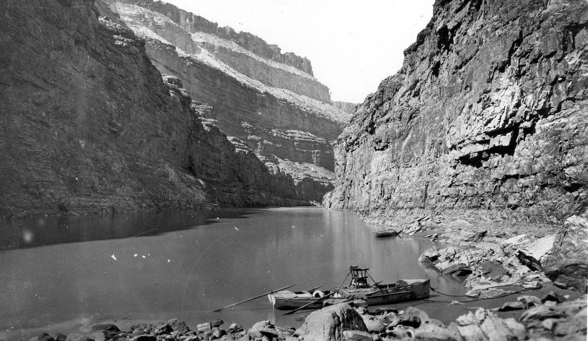 a black and white photograph of a boat docked on the shore of the colorado river amidst the sweeping landscape of the canyon