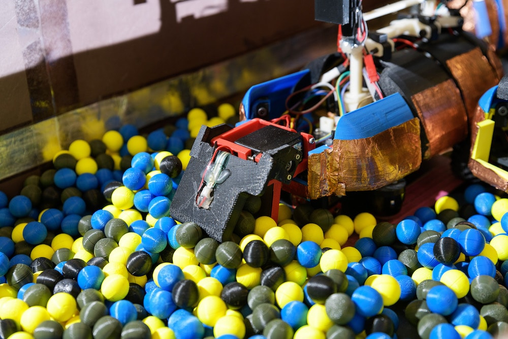 A robot ant in a pit of multicolored balls