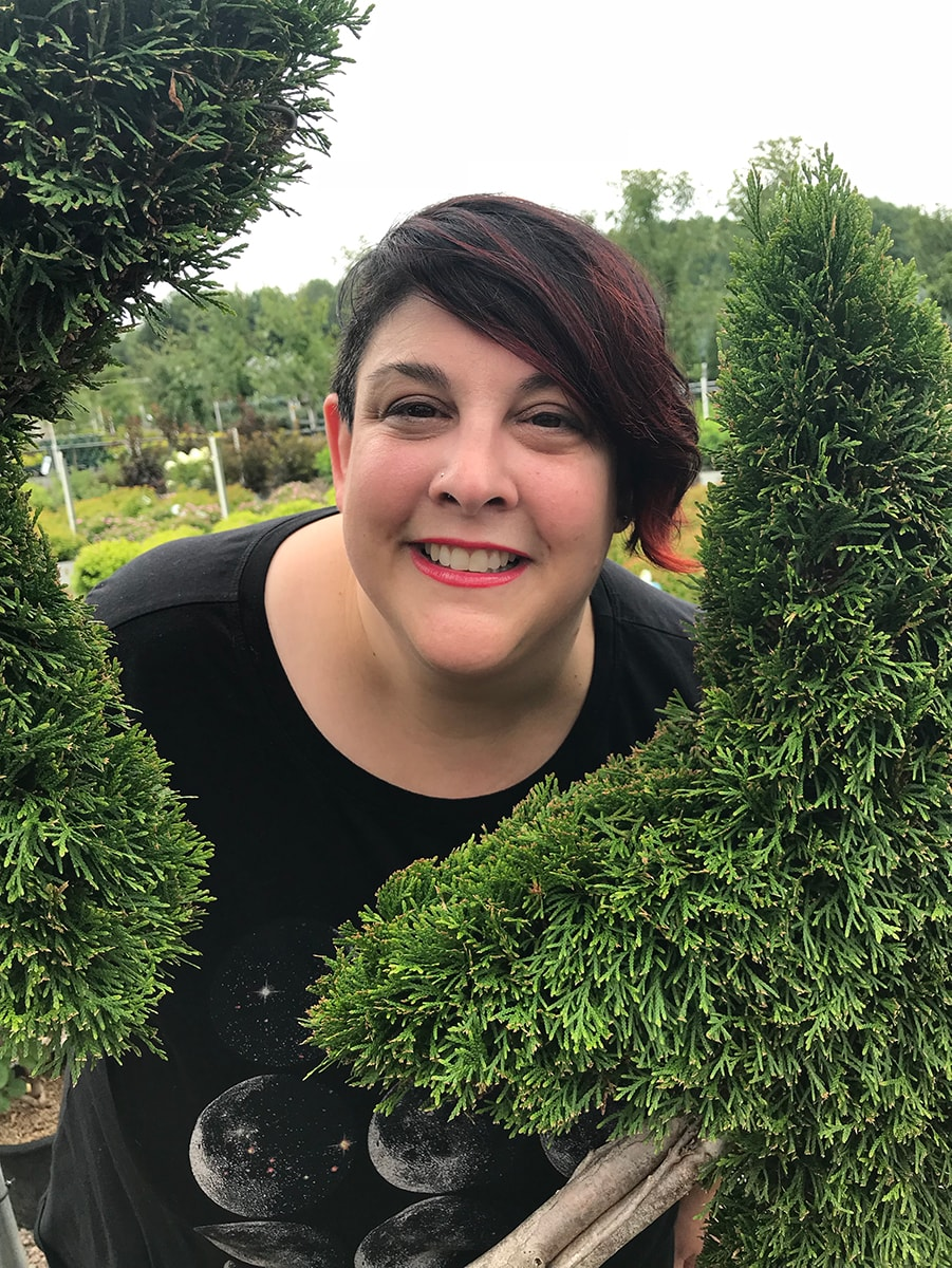 Amy Cataldo's smiling face between two topiary shrubs