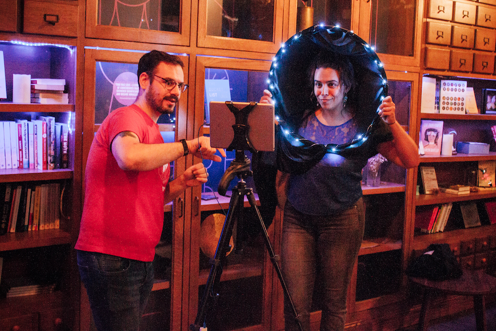 two people standing in front of an ipad taking a photo with a black hole constructed from hula hoop and fabric