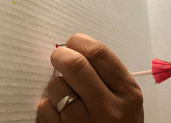 a hand placing a nail on the white board