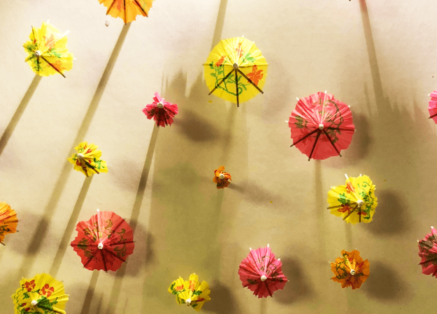 a bunch of brightly colored red, yellow, and orange umbrellas covering a white board