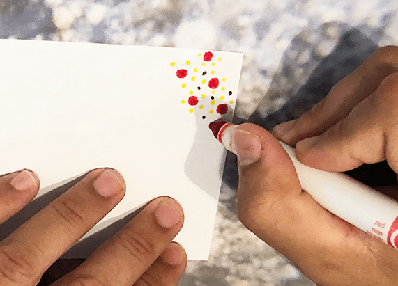 a person coloring the corner of a white square paper with a marker