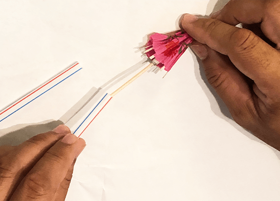 hands placing a cocktail umbrella into the end of a straw