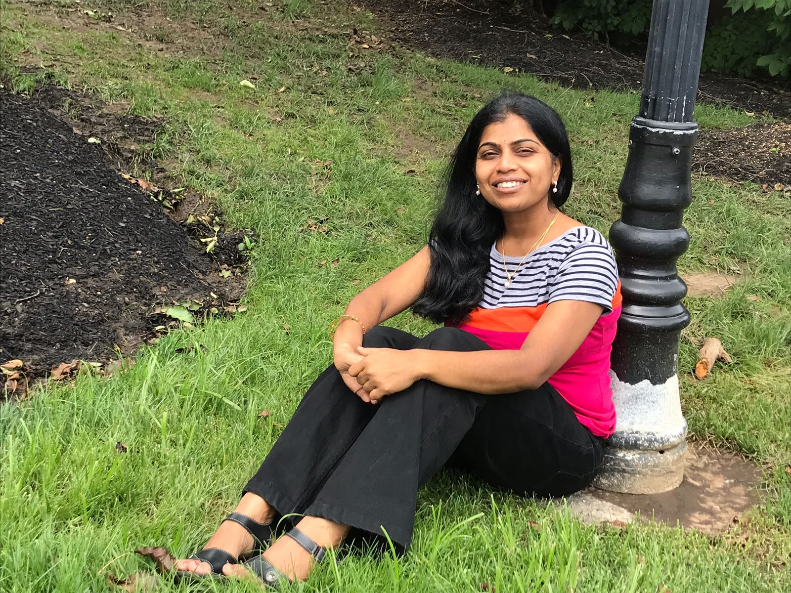Srividhya Sundaram sitting on the grass at the based of a light pole