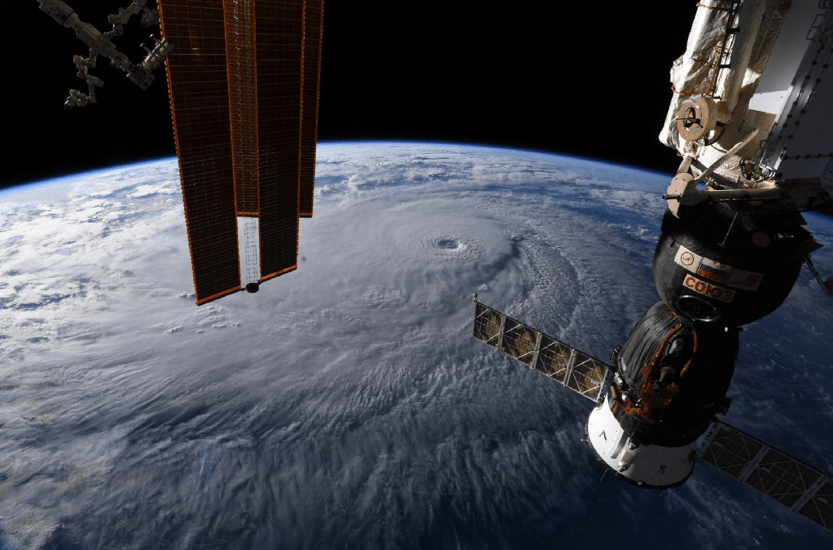 A massive hurricane seen from space, with portions of the International Space Station in the foreground