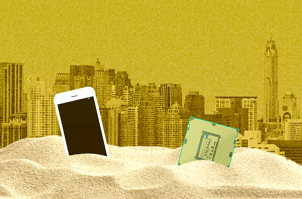 a phone and computer chip buried in sand with city in sandstorm in background