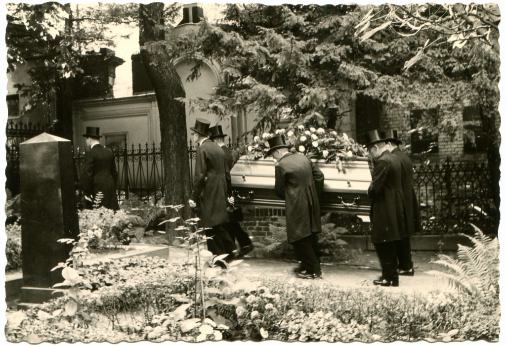 An antique photo shows a group of men in black overcoats and bowler hats, carry the coffin with the deceased at the cemetery
