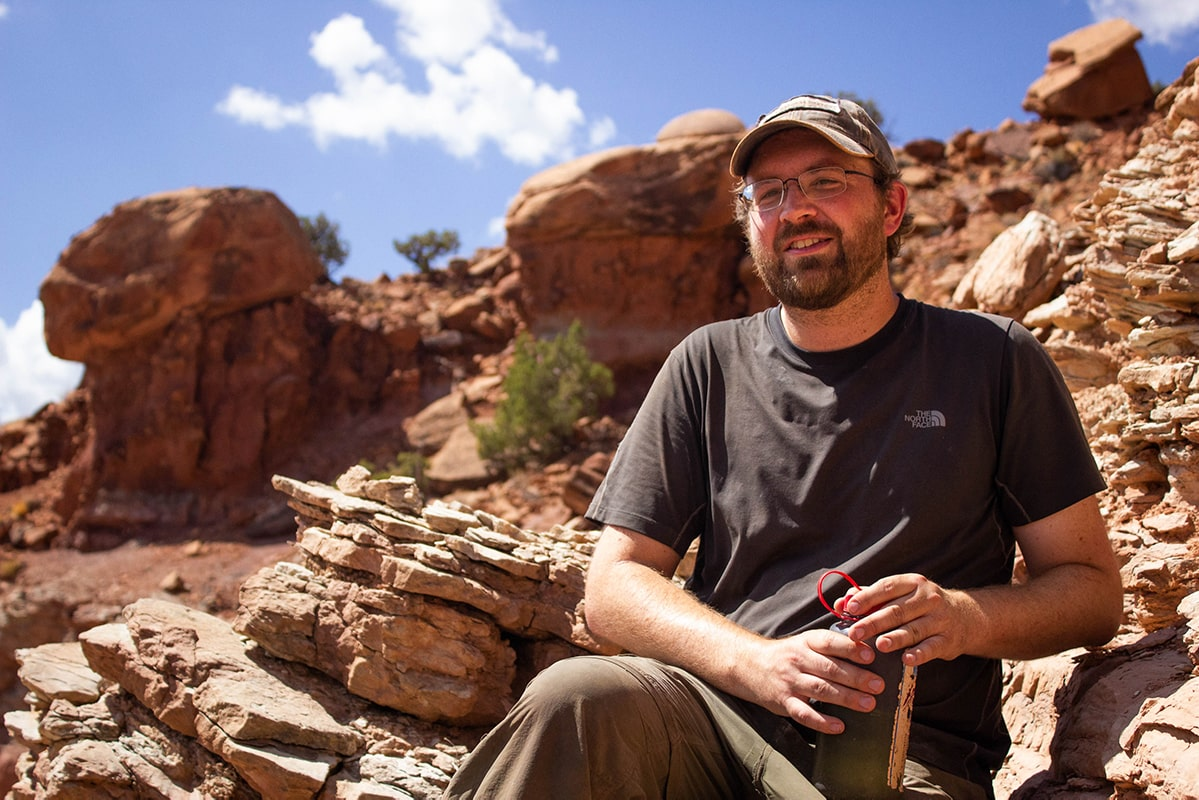 Ranall Irmis, in a baseball cap, in the desert canyons of Utah
