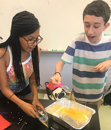 a female african american teacher assisting a student with the food collection setup of the experiment