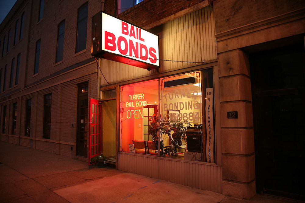 glowing red neon bail bond sign on building in dark street