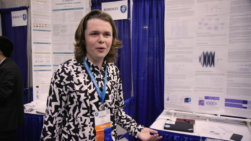 a young male student with shoulder length brown hair and a patterned black and white shirt in front of a science fair board