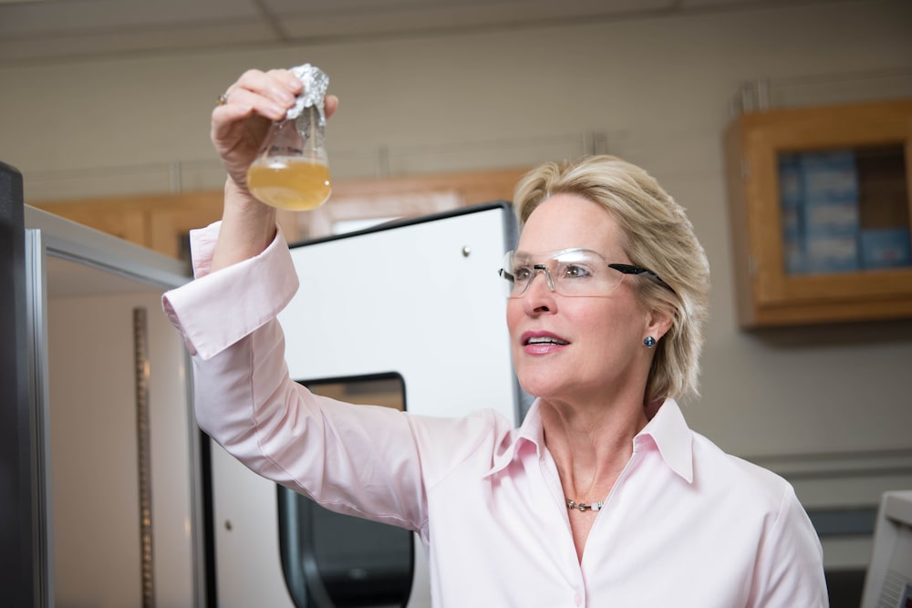 a woman in a lab wearing safety glasses holding up a beaker filled with liquid up to the light