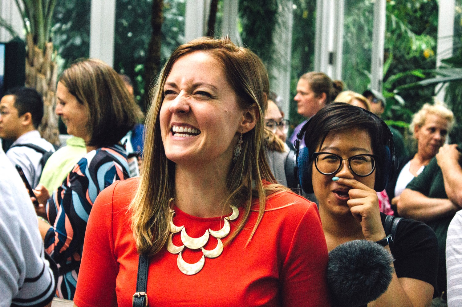 in a crowd of people, there are two women, one who's nose is wrinking and smiling, and the other, wearing headphones and carrying a microphone, is putting a finger under her nose