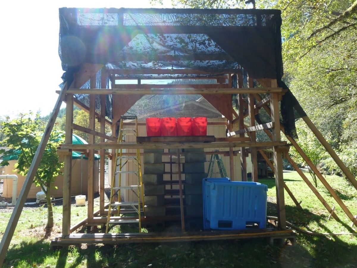 a wooden structure with magnetic coils and plastic buckets out in a grassy field