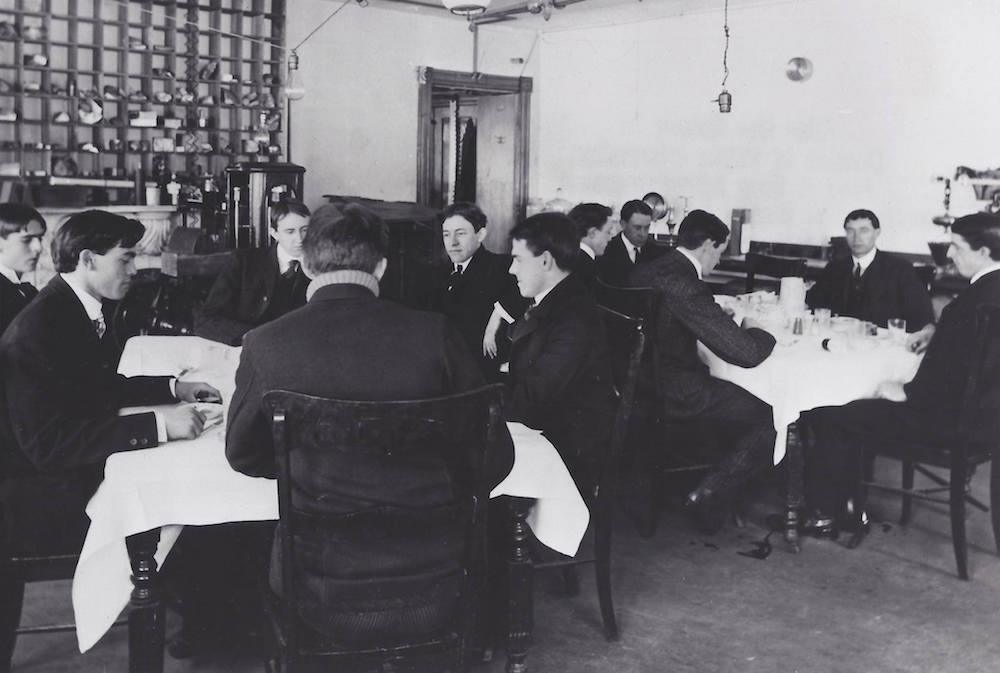 black and white photo of a bunch of men in suits sitting around tables