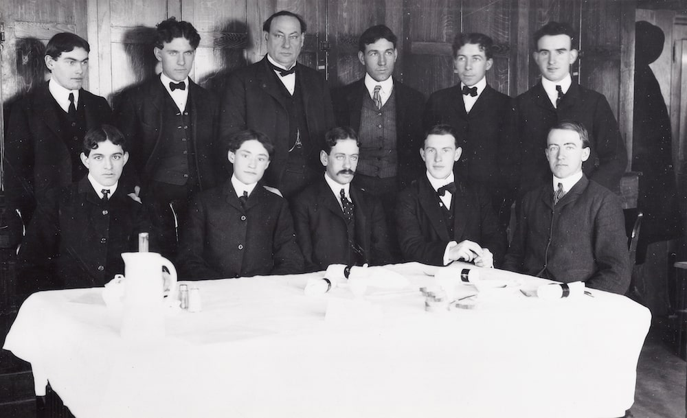 black and white photo of eleven men in suits sitting around a white table clothed table