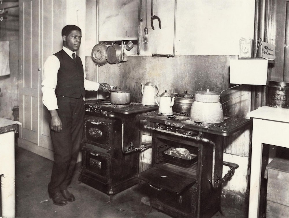an african american man in a vest and tie holding a pot in a kitchen