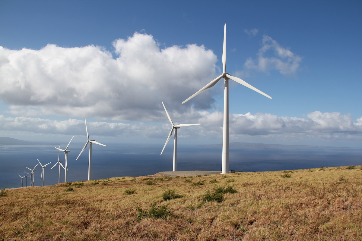 four wind turbines in a row on a ridge overlooking the ocean and a blue sky
