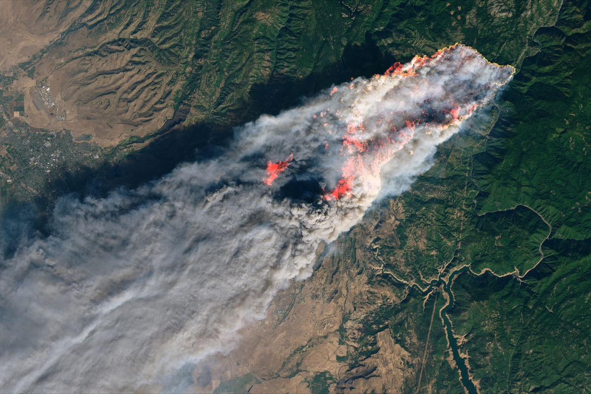 an satellite photo of a massive fire with a large trail of smoke and bright orange outlines indicating the edges of the fire