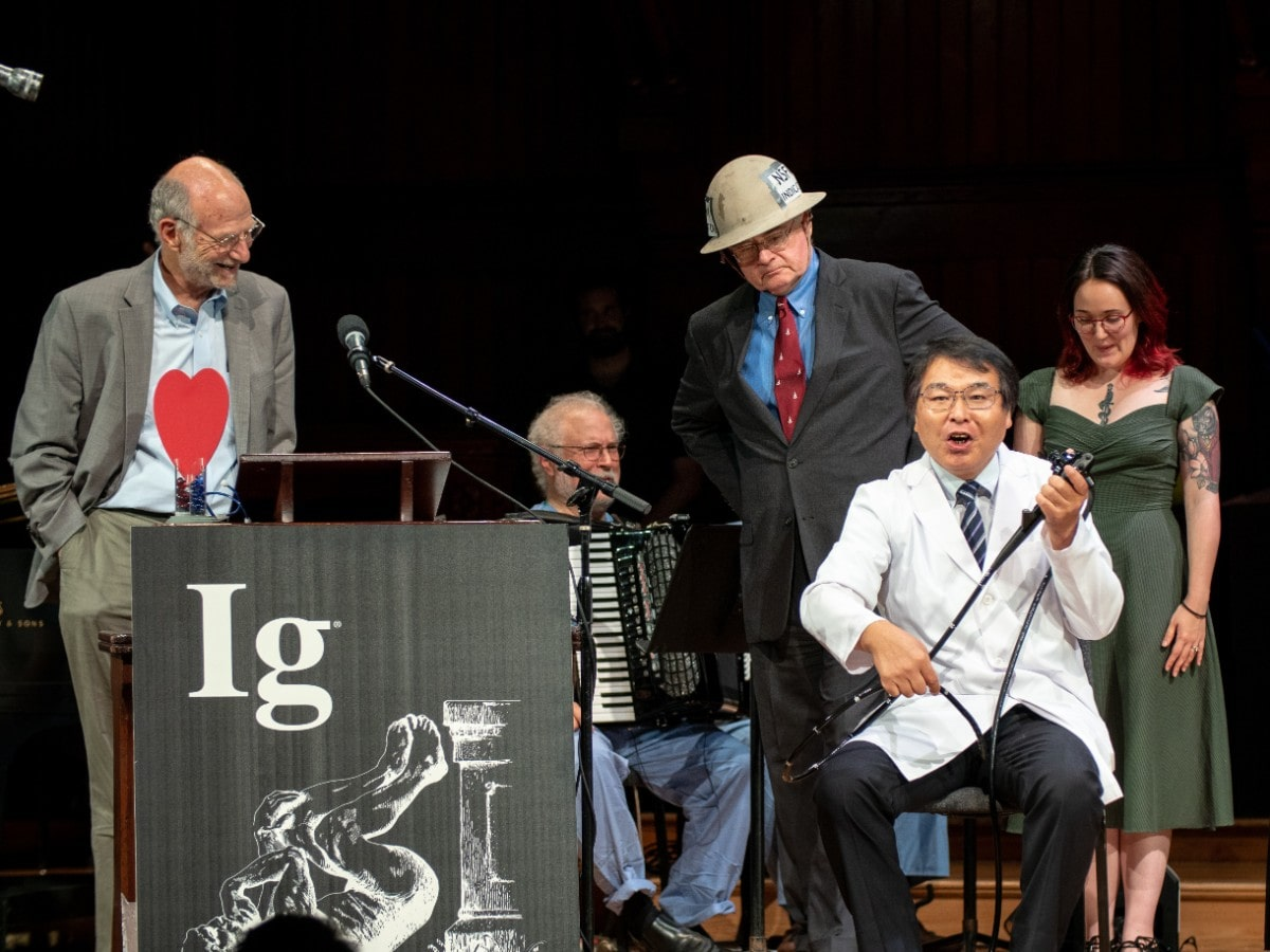 a man in a lab coat holds medical equipment and sits in a chair with an anguished face. two other men are on stage listening to him