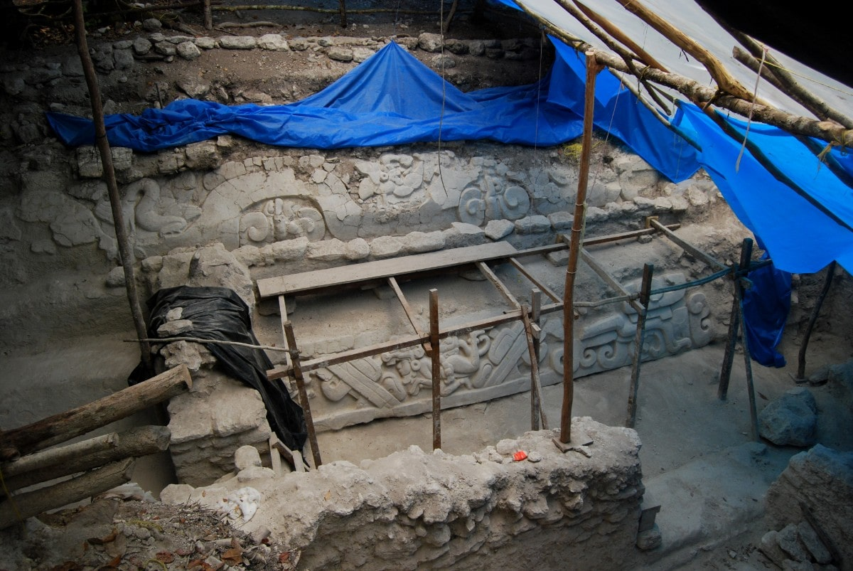 Stucco friezes at El Mirador that adorned the banks of a water-collecting system. the site has blue tarp hanging over it
