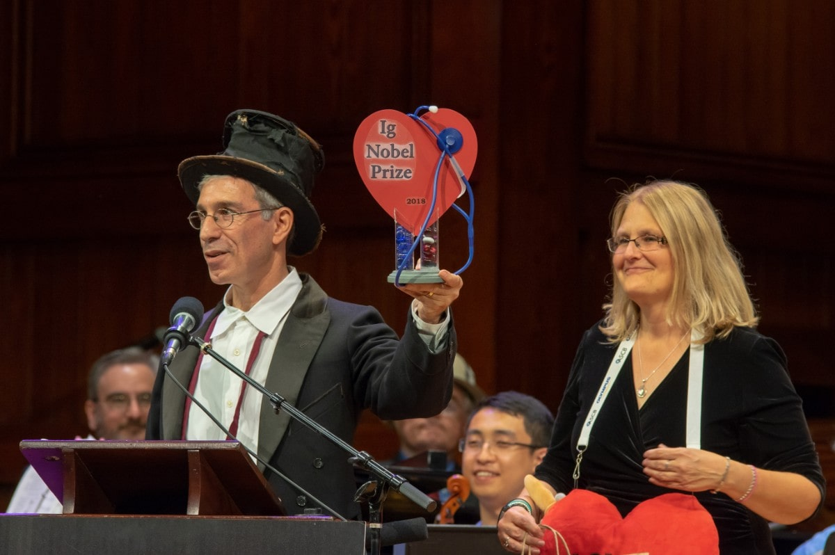 "a man in a top hat holds an award made of a cutout heart with a stethoscope around it, that reads ""ig nobel"""