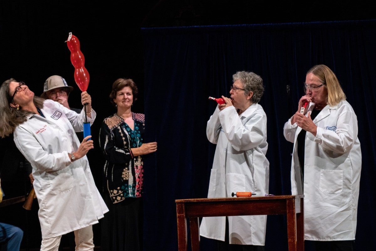 three women in lab coats doing a demonstration on stage