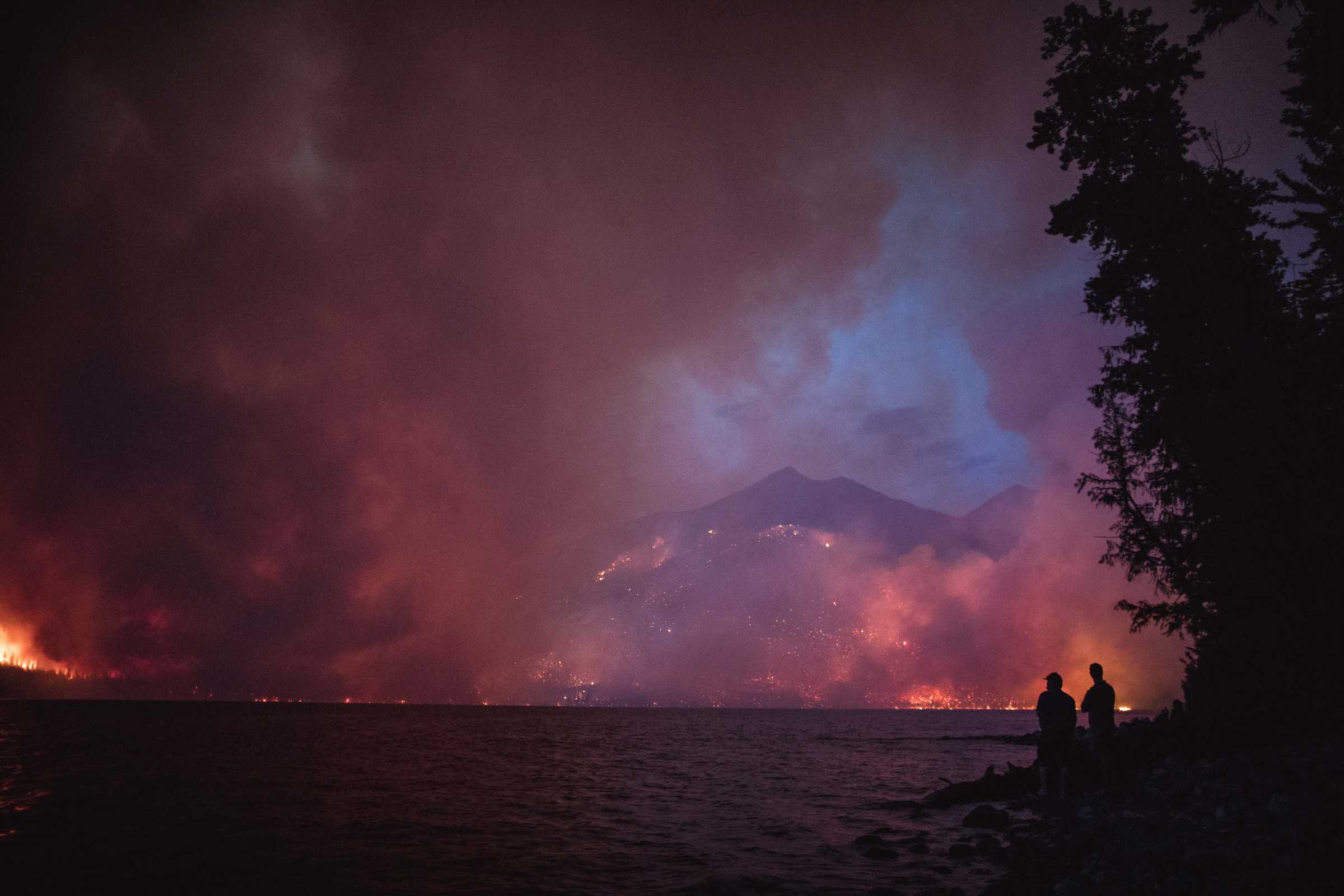 looking across a lake to massive smoke plumes obscuring mountain ranges, taken around dusk