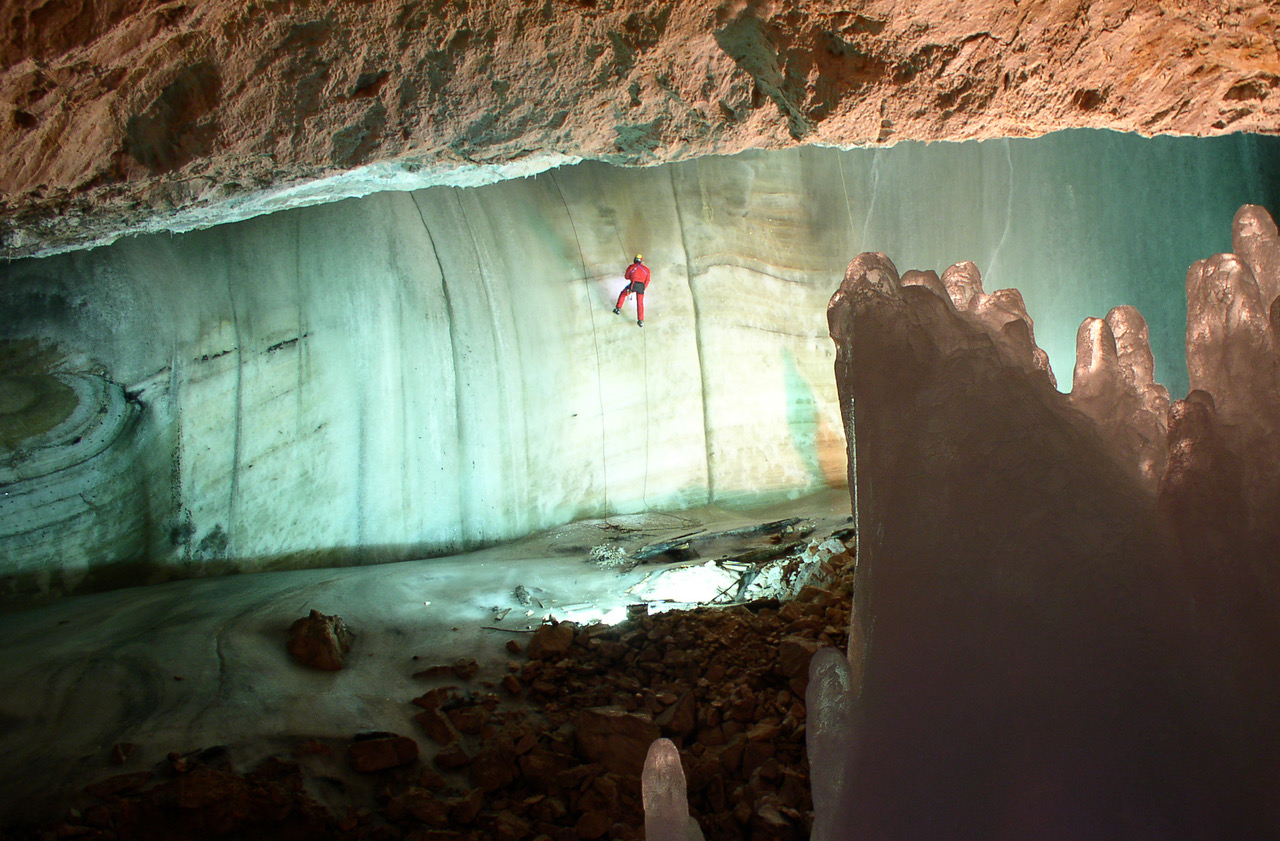 interior of cave with man in orange safety gear scaling down an ice wall