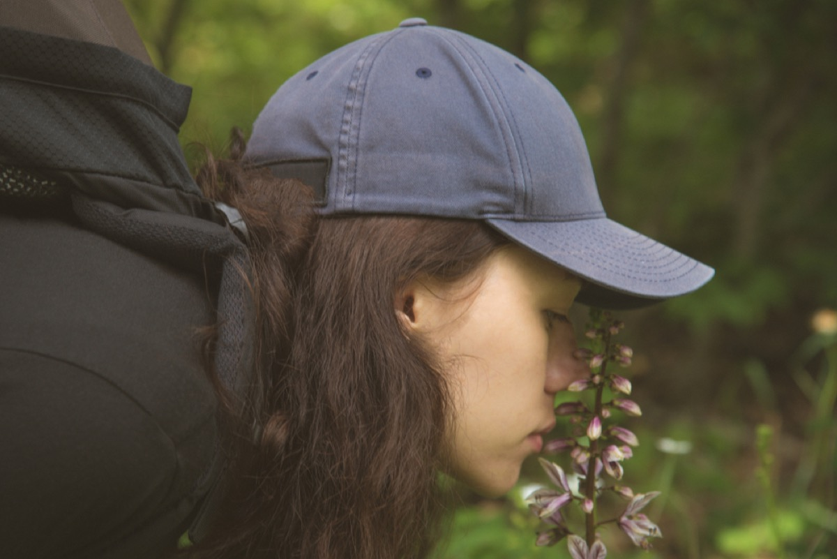 a woman with long brown hair and wearing a baseball cap smelling flowers in a forest