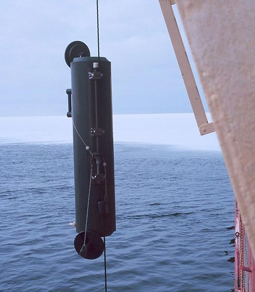 A vertical tube with a lid on either end being lowered into the water
