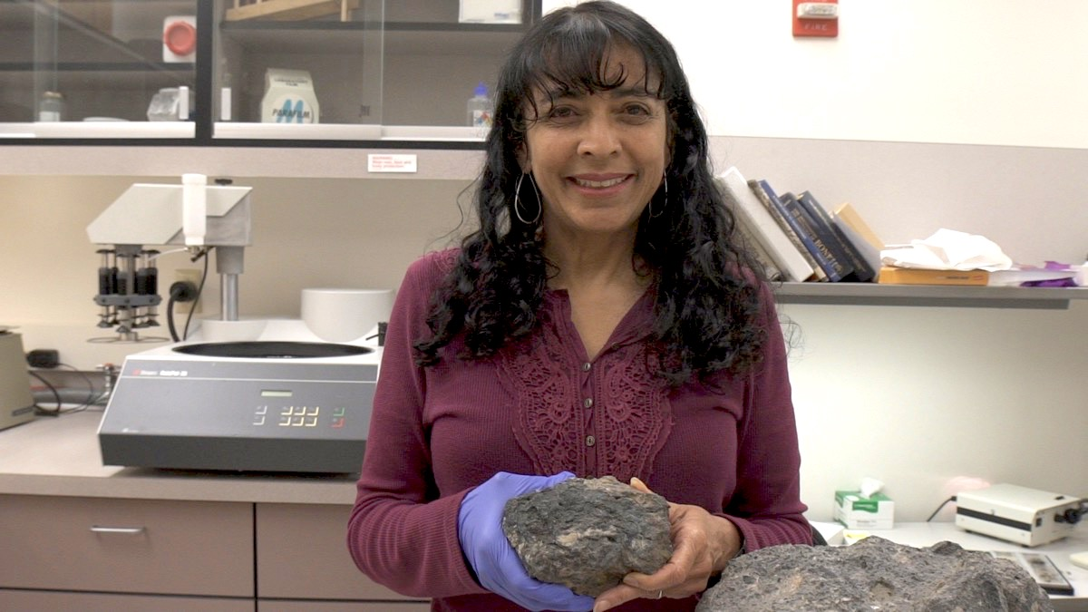 a woman holds a large rock (the coprolite) with both hands in a lab
