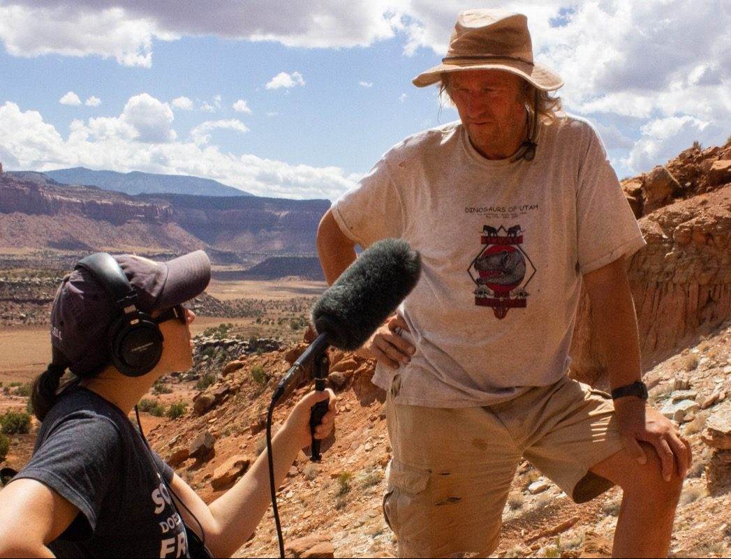 reporter katie hiler interviewing a male paleontologist on the side of a canyon