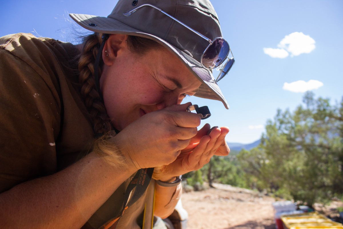 a female paleontologist uses a magnifying glass to look at a sample at a campsite in the desert