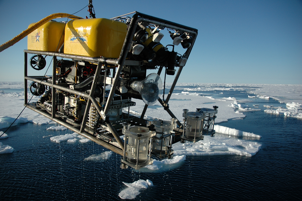 an rov on a crane with water samples, with a backdrop of sheets of ice over the ocean