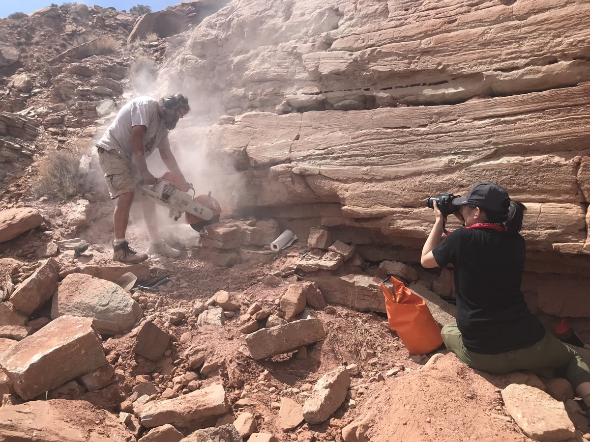 a woman crouches down next to a cliff in the desert taking a photo of a man rock sawing