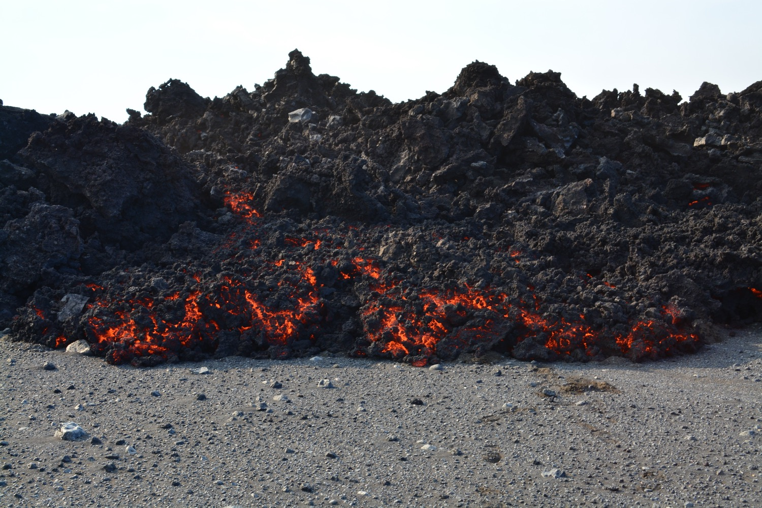 very thick gravel-y looking lava from a natural flow looks like it is approaching the camera on the sand