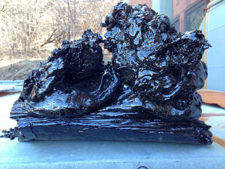 an amorphous sculpture of black, shiny lava. the unique shape looks like a black wave with sharp edges