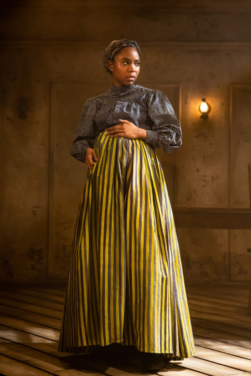 a woman of color dressed in 19th-century servant garb. she's pregnant and has her hand over her belly