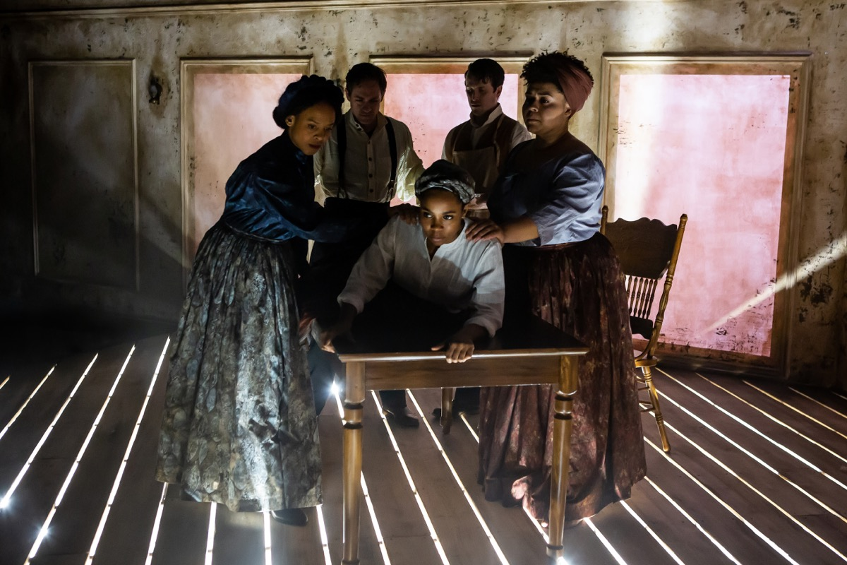 five people around a table on a stage with dramatic lighting shining through slats of the wooden floorboard. two women stand on the left of the table assisting a black woman lying on her belly on the table, while the two men are medically examining her