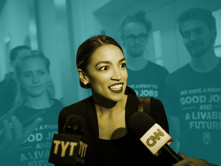 Ocasio-Cortez in the foreground flanked by two tv mics with students behind her