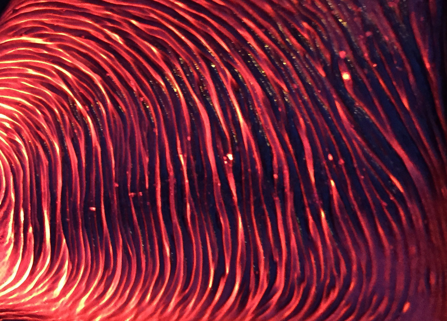 a close up of bright red glow peaks between ripples and folds of hot lava.