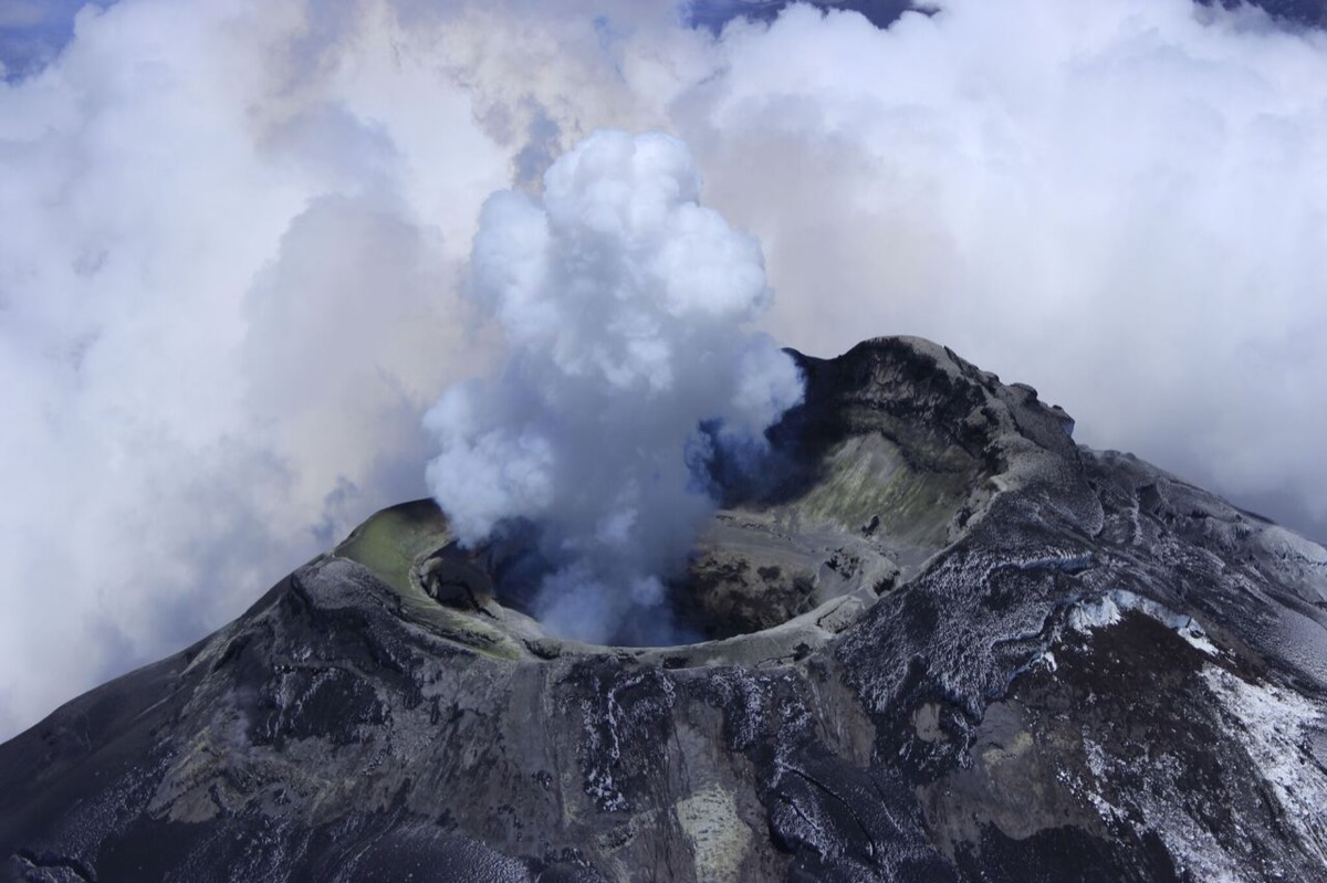 close up photo of volcanic crater spewing ash and residue