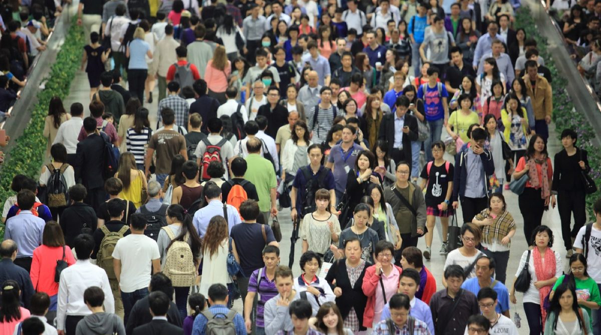 a crowd of people in hong kong going in and out of a tunnel in a subway station during rush hour