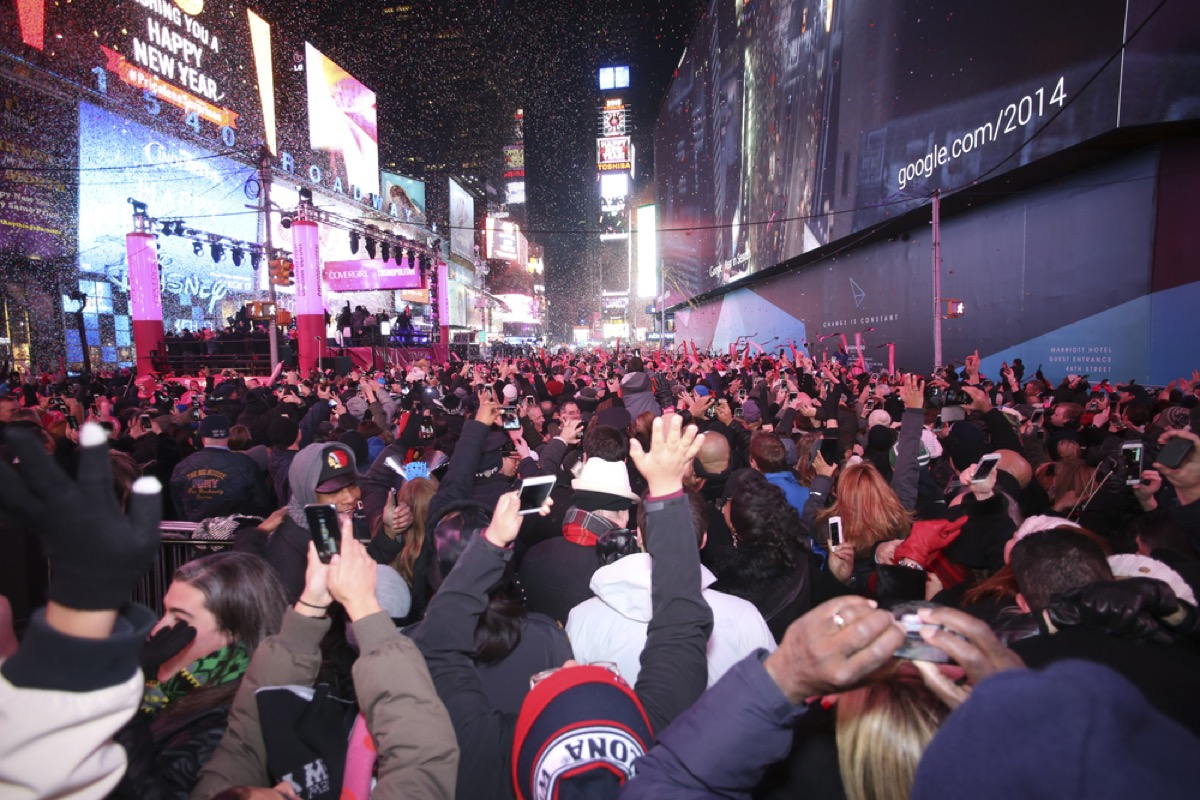 a massive crowd of people celebrating and raising their arms up at midnight with confetti in the air. in new york city