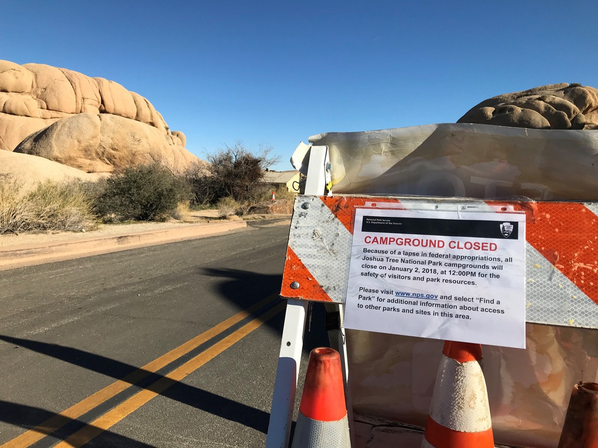 "a road sign that says ""campground closed because of a lapse in federal appropriations, all Joshua tree national park campgrounds will close on January 2, 2018, at 12:00 pm for the safety of visitors and park resources. Please visit www.nps.gov and select find a park for additional information about access to other parks and sites in this area."" the sign is on a road next to large sandstones in the park"