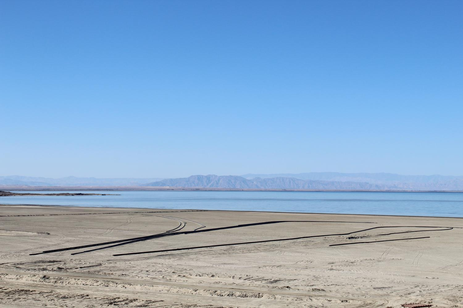a good stretch of sand and a large body of water with mountains beyond that