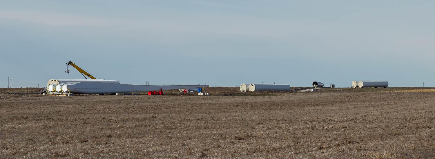 several long pieces of turbines laying on their sides in a field